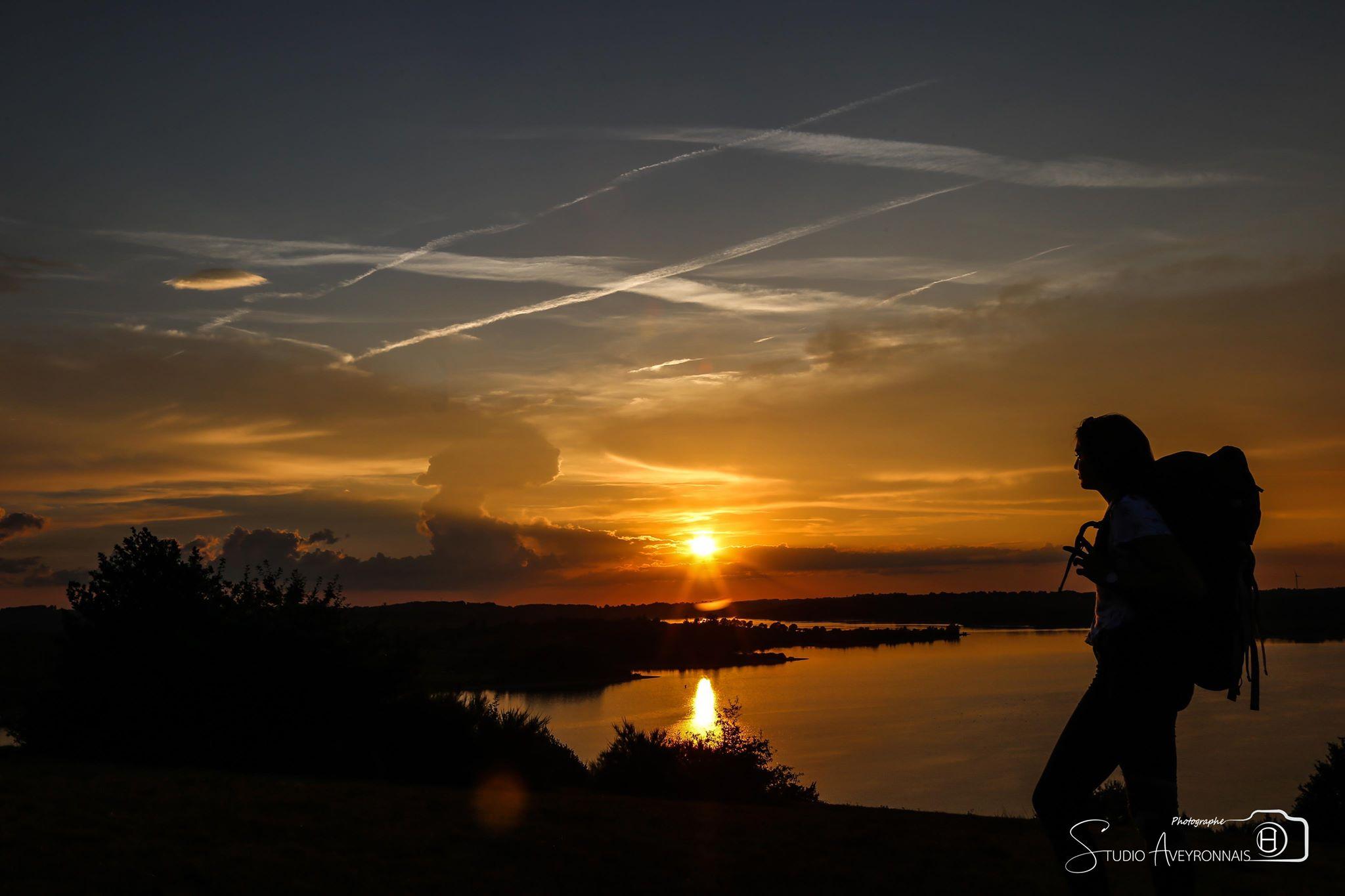 Randonneuse et coucher de soleil sur le lac de pareloup, point de vue de la Vierge du Lac